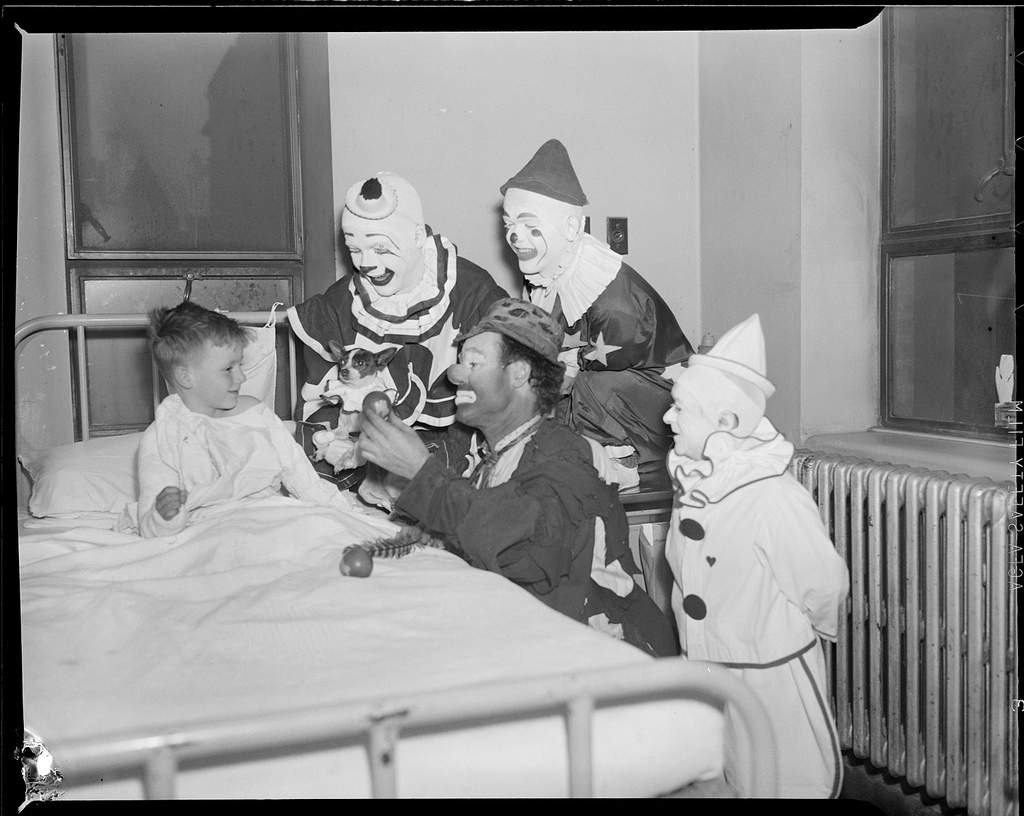 Circus clowns visit sick boy. CC photo Boston Public Library.