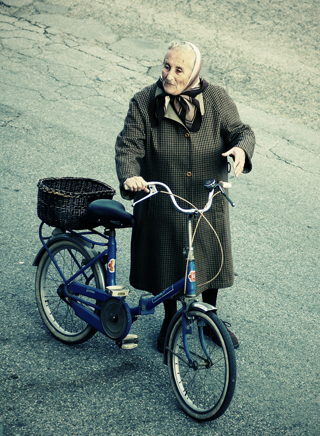 Picture of an old woman and a bicycle.