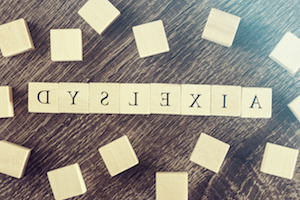 Dyslexia word formed with wooden blocks. Reading difficulties concept. Cross processed image with shallow depth of field