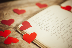 Red heart shapes on a handwritten old journal.