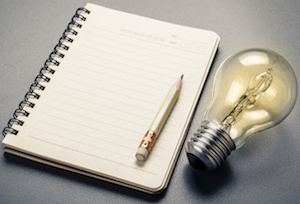Creative Writing, Pencil on notebook with glowing light bulb